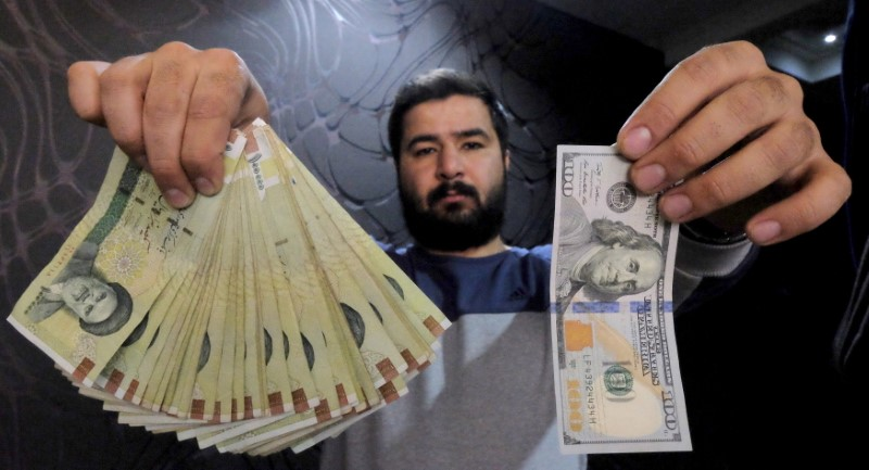 © Reuters. Money changer poses for the camera with U.S hundred dollar bill and the amount being given when converting it into Iranian rials, at a currency exchange shop in Tehran's business district, Iran