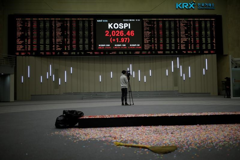 © Reuters. A journalist films the final stock price index after the ceremonial closing event of the 2016 stock market in Seoul