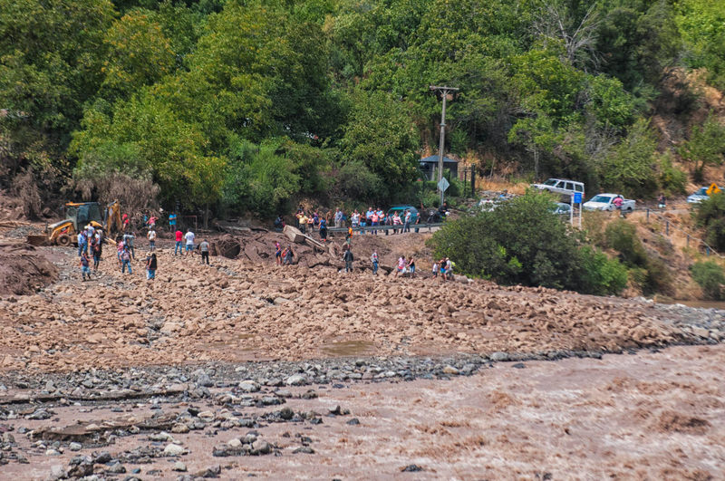 © Reuters. People walk along a damage road after a flood near Santiago, Chile